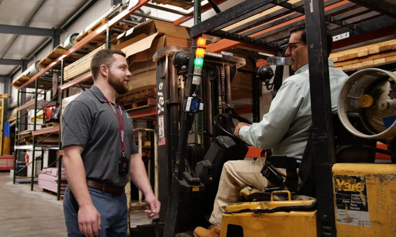 worker approaches forklift driver